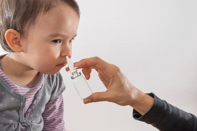 Впрыскивание спрея в носовые ходы ребенку