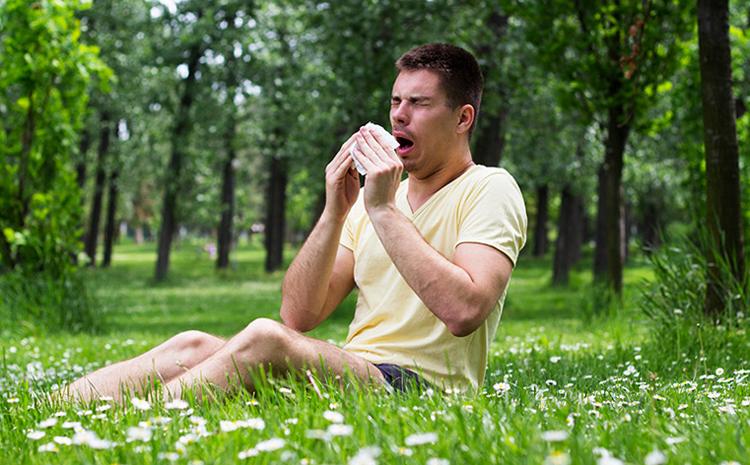 Мужчина на траве чихает